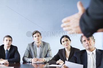 Business associates listen as colleague makes presentation during meeting