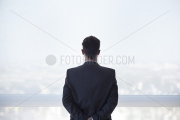 Businessman looking out high rise window at view of city below  rear view