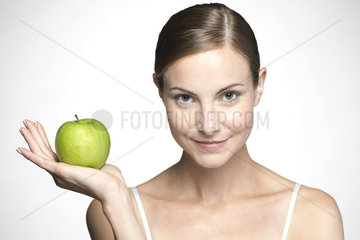 Young woman holding up green apple