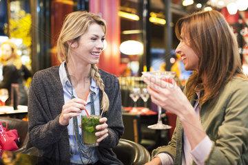 Women enjoying cocktail at bar
