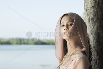 Young woman leaning against tree  wearing head scarf