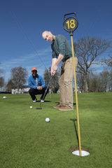 Gluecksburg  Deutschland  Golfanfaenger mit Golflehrer auf dem Uebungsplatz beim Putten
