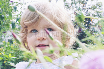 Little girl in flower garden  portrait