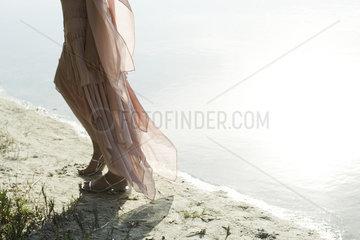 Woman in dress walking along shore  low section