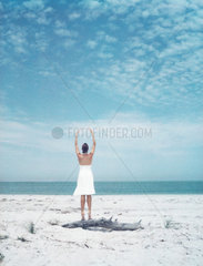 Woman standing on driftwood at the beach  arms raised  rear view
