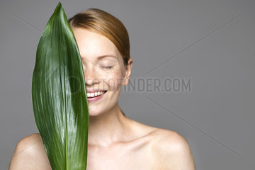 Young woman holding up leaf concealing part of face