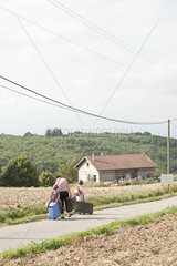 Mother and children wandering through countryside  dragging suitcases behind them