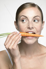 Young woman biting into carrot