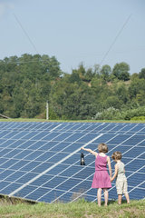 Children standing together in front of solar panels  girl holding old-fashioned latern