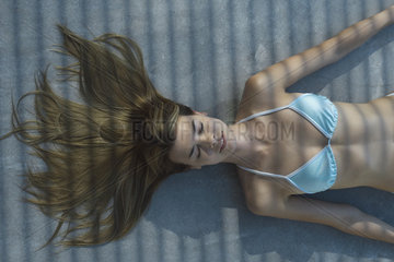 Woman lying on ground in shade