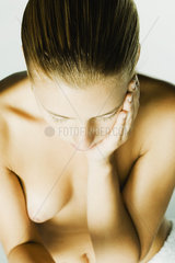 Nude woman holding face  high angle view