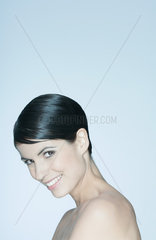 Woman with short hair  bare shoulders  smiling at camera  portrait