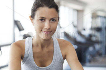 Young woman using exercise machine at gym