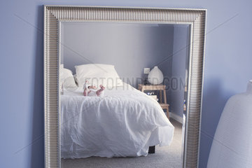 Mirror reflection of baby lying on bed