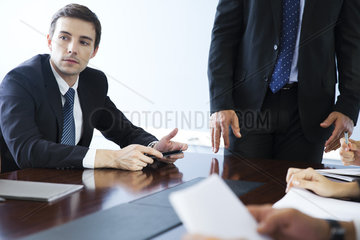 Businessman listening to collegues speak during meeting