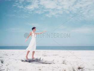 Woman balancing on driftwood on beach  arms out