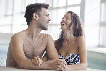 Couple relaxing together in indoor swimming pool