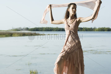 Young woman wearing dress  holding up scarf  lake in background
