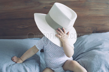 Baby with face obscured by large hat