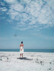 Woman standing at the beach  looking at horizon  rear view