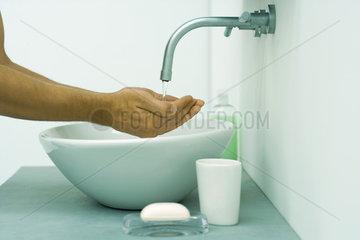 Man's hands under running water in bathroom sink  side view
