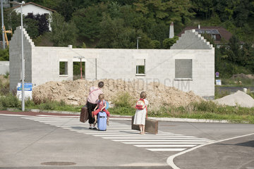 Mother and children walking in street toward unfinished house   dragging suitcases behind them