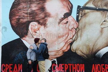 Berlin  Deutschland  Zwei junge Maenner kuessen sich vor einem Wandbild in der East Side Gallery