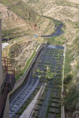 Blick von einer Staumauer auf eine Wasserfuehrung am King Talal Damm in Jordanien