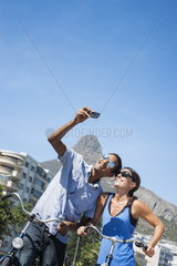 Mixed race male and Caucasian woman couple taking a Selfie photo in front of Lion's Head mountain at Camp's Bay beach  Cape Town  South Africa  Africa