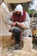 Buetzow  Deutschland  ein Holzschnitzer macht eine Holzschale beim Klosterfest