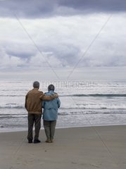 Elderly couple looking out over the ocean