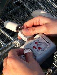 Junge Frau loest Einkaufswagen mit Einkaufschip aus