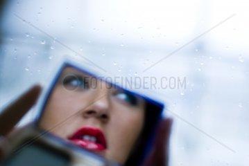 Spiegelbild einer huebschen dunkelhaarigen Frau mit blauen Augen und Lipgloss