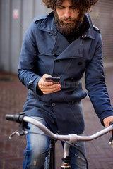 Junger Mann im Trenchcoat auf dem Fahrrad