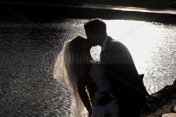 Berlin  Deutschland  Silhouette eines Brautpaars an einem See
