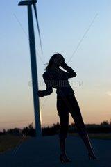 Silhouette einer jungen Frau auf einer Strasse mit Windrad