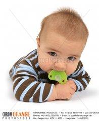 Baby mit Schnuller auf dem Bauch liegend