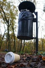 Berlin  Deutschland  Leerer Kaffeebecher liegt vor einem vollen Muelleimer im Wald