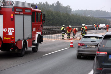 Allersberg  Deutschland  Feuerwehrmaenner beseitigen nach einem Autounfall auf der A9 eine Oelspur