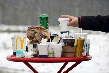 Hermsdorf  Deutschland  Leere Kaffeebecher  Getraenkedosen und zerknuellte Papiertueten auf einem Rastplatz-Tisch
