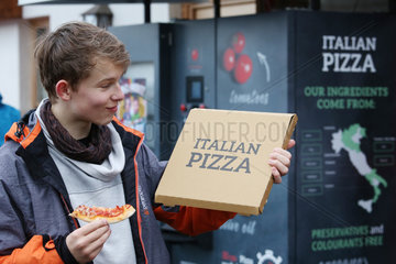 Reischach  Italien  Junge zeigt stolz den Karton seiner aus einem Automaten gezogene Pizza