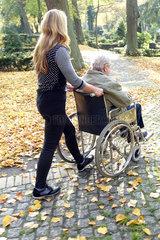 Berlin  Deutschland  Frau schiebt einen alten Mann im Rollstuhl