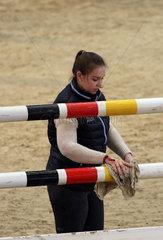 Neustadt (Dosse)  Maedchen saeubert eine Hindernisstange im Springparcours