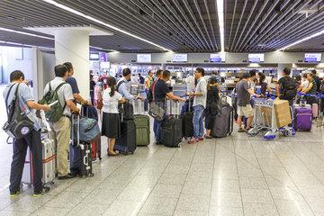 Reisende mit Rollkoffer am Checkin Schalter