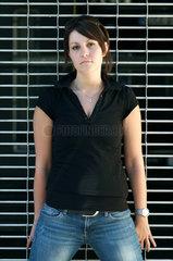 Berlin  junge Frau steht cool vor einem Rollgitter
