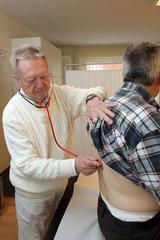 Bad Segeberg  Deutschland  Dr. Uwe Denker untersucht einen Patienten in seiner Praxis ohne Grenzen