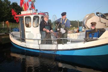 Flensburg  Deutschland  Nebenerwerbsfischer saeubern ihre Netze nach getaner Arbeit am Steg in Fahrensodde
