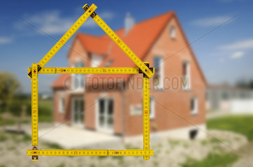 new built house under construction with symbolic yard stick
