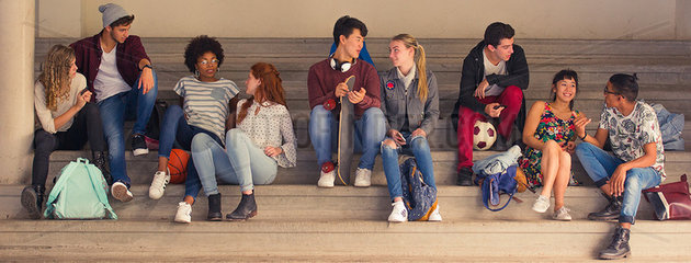 College students hanging out and chatting together on bleachers