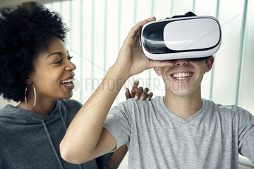 Young man using virtual reality simulator with friend